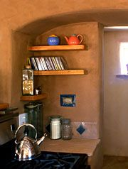 Mud earth plaster on an adobe wall with straw bale arch