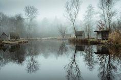 Mysterious Lakefront Habitations  Avec son brouillard quasi constant ses arbres dénudés et ses petites maisonnettes regroupées autour dun lac miroir le village de Sződliget en Hongrie ressemble en tout point à un village de sorcières comme il en existait autrefois dans certaines régions reculées. Photographies signées Viktor Egyed.               #xemtvhay