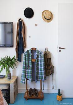 Cabides espalhados pela parede organizam as peças e acessórios do morador.