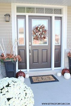 Heather of Setting for Four picked up the silvery-gray finish of her front door with her autumn decor. Birch branches in the urns, metallic-painted pumpkins, and white pumpkins are cool and chic.