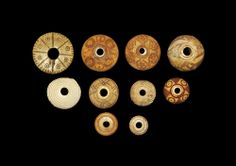 """Egyptian Coptic Bone Spindle Whorls. 5th-8th century AD. A mixed group of spindle whorls comprising: one discoid, spokes and ring-and-dot designs; one discoid, incised concentric circles; one plano-convex, bird motifs; one similar, six lozenges with ring-and-dot motifs; one similar concentric circles and ring-and-dot designs; one similar, chevron motifs; two similar, ring-and-dot and hatched triangle motifs; one similar, concentric ribbing. 47 grams, 15-32 mm (1/2 - 1 1/4"""")."""