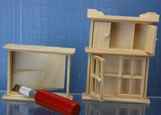 A sturdy hobby knife cuts the back of the top part of a dolls house hutch free from the basic box.