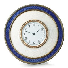 A Fabergé two-colour enamel, silver-gilt and seed pearl clock, workmaster Michael Perchin, St Petersburg, circa 1890, circular, enamelled in translucent pearl white within blue over wavy engine-turning, reeded, chased leaf and seed pearl borders, ivory back, scroll strut, struck with workmaster's initials and Fabergé in Cyrillic, 88 standard.