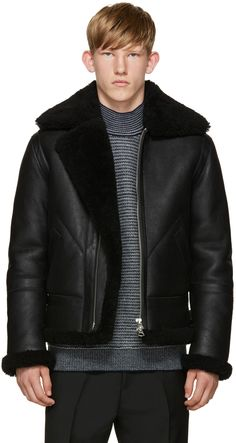 Long sleeve lamb shearling coat in black. Tonal leather trim throughout. Adjustable pin-buckle fastening at stand collar. Zip closure at front. Welt pockets at waist. Perforated detailing at underarms. Adjustable cinch-straps with pin-buckle fastening at back hem. Zip pocket at interior. Fully lined. Silver-tone hardware. Tonal stitching. 100% lamb shearling.