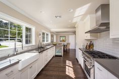 Traditional galley kitchen with farmhouse sink, walnut flooring, white cabinets and subway tile backsplash