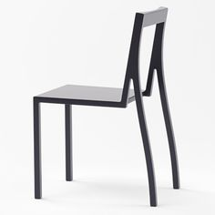 Heel chair by Nendo | Made from wood and lacquered in black, the Heel chair has two straight legs at the front, while the pair at the back are curved to meet the central section of a hollow backrest.