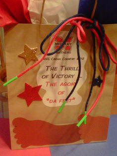 """We could not find a fun cross country banquet table decoration.  So we made our own.  Simple brown bag with school color tissue paper tucked inside.  Footprint cut-outs around the perimeter of the bag celebrate the season of running and the shoe laces we made from parachute cord embellished with neon duck tape.  Mom came up with """"The thrill of victory...the agony of DA FEET""""."""