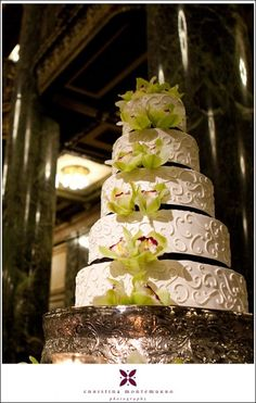 Green cymbidiums accent this 5-tier white and black wedding cake.