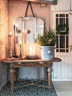 Årets adventsljusstake är arrangerad i ett gammalt träfat fyllt med av nötter. Innanför den gamla dörren med lingonriskrans finns skafferiet.