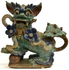 """CHINESE POLYCHROME GLAZED CERAMIC FOO LION 19th c., possibly a roof tile, decorated in flowers and resting his paw upon the world, approx 14""""h, 14.25""""w"""