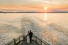 Bride and groom stand at the stern of the ferry after being married watching the sun set behind the Olympic Mountains.