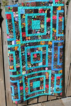 """This whimsical scrap quilt is filled with all sorts of black background fabrics sprinkled with bright colors. Various shades of blue and turquoise solids are used in a geometric pattern throughout the quilt to add even more fun.  This quilt measures 47"""" x 63"""" - perfect for a lap quilt or to use at the foot of the bed for those cooler nights when you need a little extra warmth. It would be cute in a child's bedroom or a great gift for a family movie night."""