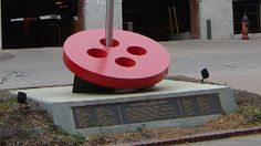 ButtonArtMuseum.com - Artist/Designer: Dave Stevens Dates: October 4, 2002 Sculpture depicts a tall stainless steel threaded needle stitching into a large red button. The button is red with four holes and is placed at an angle sloping downward toward the north side of the sculpture. The needle symbolizes the buildings nearby which were the heart of Kansas City's garment district and once made over 25% of the clothing in the United States. W. 8th St. & Broadway