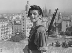 July 21, 1936, Mari Ginestà, 17, a member of the Juventudes Comunistas (Iberian Communist Youth), stands armed on the roof of the Colón hotel in Barcelona mere days into the Spanish revolution against Franco's military coup. The picture was taken by Juan Guzman (who was born Hans Gutmann in Germany before going to Spain where he photographed the International Brigades).