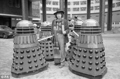 Tom Baker as the fourth Doctor Who, surrounded by Daleks in the BBC TV Centre car park. In his first year in the role, Baker would meet the Doctor's most deadly adversaries in 'Genesis of the Daleks'. (C) BBC Doctor Who Series 7, New Doctor Who, 4th Doctor, Classic Doctor Who, White City London, Tv Center, Centre, William Hartnell, Jelly Babies