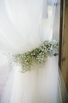 Baby's Breath looks beautiful in all sorts of places and spaces! Baby's Breath gives charm to tie back the curtain here, and would look lovely in centerpieces and other arrangements throughout the venue. This idea would work well with other types of flowers as well. Shop Baby's Breath and other popular wedding flowers and wholesale flowers year-round at GrowersBox.com!