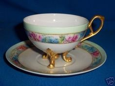 This beautiful hand-painted footed cup 2 1/2-inches high and the saucer is 5 3/4-inches in diameter. A wide border with pink roses and white flowers in a shaded blue-to-green background sits near each