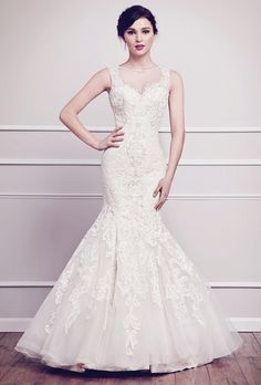 Brides: Kenneth Winston. Fit and flare silhouette gown covered in soft cotton lace from the bateau neckline to hem and paired with intricate bead work. The back consists of a sheer illusion detailed with cotton lace, sprinkled with jewels and satin covered buttons. Zipper back.��See More Kenneth Winston Gowns