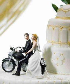 """Motorcycle Get-away Wedding Couple Figurine  This romantic wedding couple are seated on a classic motor bike that has been magnificently crafted and includes a miniature Just Married license plate along with actual paper pom poms delicately tied to the back fender. Hand painted porcelain.  Size: 5.5"""" Long, 5"""" Tall, Weight: 9.6 oz, Base: 5-1/2 x 2-3/4"""