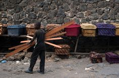 A boy carried planks of wood past coffins on display on a street in Goma, Democratic Republic of Congo. Demand for coffins has increased recently amid clashes between soldiers and rebels with the M23 movement. Photography by: Phil Moore/Agence France-Presse - Getty Images