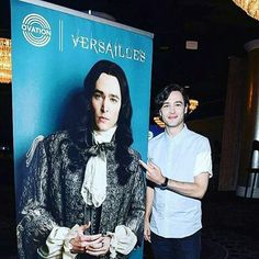 Alexander Vlahos & a poster of his character Monsieur Philippe Duc D'Orleans in Versailles