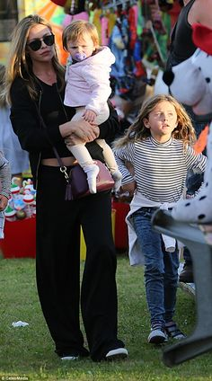 Abbey Clancy shows off her taut abs in low-key ensemble as she takes baby daughters Liberty and Sophia to the funfair with lookalike sister Elle | Daily Mail Online