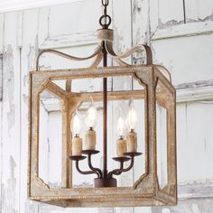 A distressed wood frame in washed gray with golden trim is held aloft by four scrolled iron arms giving this fixture a romantic, weathered cottage-style look and feel. Place this boxy lantern-style chandelier in a foyer or group several above an island or dining table. Farmhouse Chandelier, Lantern Chandelier, Rustic Chandelier, Farmhouse Lighting, Chandelier Shades, Hanging Lanterns, Rustic Farmhouse, Kitchen Lighting, Kitchen Chandelier