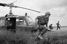 Capt. Donald R. Brown of Annapolis, Md., advisor to the 2nd Battalion of the 46th Vietnamese regiment, dashes from his helicopter to the cover of a rice paddy dike during an attack on Viet Cong in an area 15 miles west of Saigon on April 4, 1965 during the Vietnam War. Brown's counterpart, Capt. Di, commander of the unit, rushes away in background with his radioman. The Vietnamese suffered 12 casualties before the field was taken.
