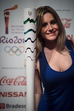 #RIO2016 A woman poses with the newly introduced Rio 2016 Olympic torch at Jockey Club Brasileiro in Rio de Janeiro Brazil on July 3 2015 The recycled...