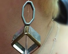 Glass cube trimmed in gold, with silver metal oval on rose gold earwire