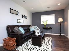 This spare gray living room is accented by a darker gray accent wall, and livened up with a geometric area rug. The simple furnishings allow the colors and light to stand out.