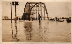 "Bridge during 1903 flood. The sign on the bridge reads: ""Speed Limit Not Faster Than A Walk"". A member of the Baker family is in the photo 