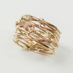 """Threads of life"" ring in red and yellow gold with a lovely brown diamond. Www.hoogenboombogers.com"