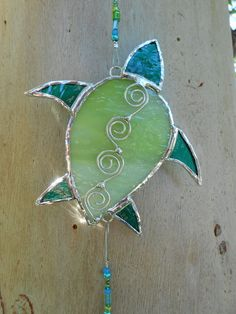 This Stained Glass Turtle Suncatcher is done Green, and Aqua Green glass with wire embellishments across the its shell. It hangs from a Green &