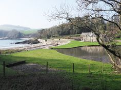 View of Polridmouth Cottage by Polridmouth Cove, England, which has a lake, an old watermill (once ground grain for the Menabilly Estate - private retreat once home to author Daphne du Maurier), a footbridge over a little fall, and overlooks a beach and the sea.