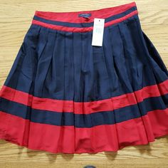 Size 10 Tommy Hilfiger pleated skirt w/tags Navy blue and cherry red pleated Tommy Hilfiger skirt. Red lining, size 10 and never worn. Tommy Hilfiger Skirts A-Line or Full