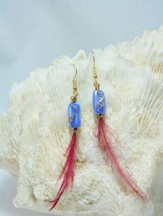 Pendiente dorado de gancho abierto, con cristal azul, filigrana dorada y pluma roja.