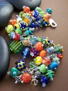 Lots of color and movement with this piece! Artisan lampwork with Swarovski Crystal and Sterling Silver charm bracelet.