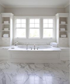 Master bathroom with white wood paneled drop-tub flanked by white vertical  bathroom cabinets. Gray bathroom walls paint color and marble tiles  bathroom ...