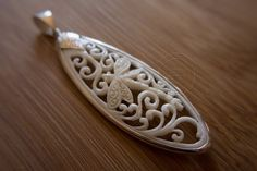 Jewellery charms grouped with the motif of a Dragonfly and floral ornaments in an oval shape. Carved with Balinese artistry from Buffalo Horn and in 925 sterling silver.  25 x 70 mm  Leather collar 60 cm with silver clasp