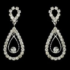 """Two lovely silver plated loops adorned with dozens of dazzling clear crystals make these fabulous clip-on dangle earrings a perfect choice for weddings, proms or any formal event. They will bring that extra touch of sparkle you've been searching for! This style earring comes in pierced and clip on.  Size: 2"""" long x 0.75"""" wide"""