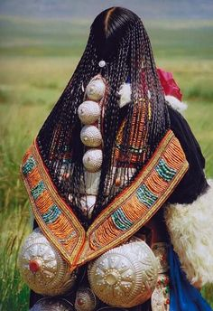 Tibetan nomad woman with her hair plaited in 108 braids (or as close as possible) to represent the 108 volumes (teachings) of the Tibetan holy book, the Kan Djur.  | Photographer unknown