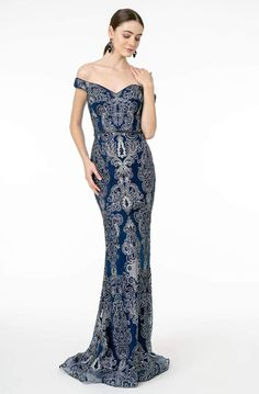 Look stunningly beautiful in this sophisticated Elizabeth K GL2922 evening dress. The whole ensemble is designed in glitter pattern as the fitted bodice features an off-shoulder neckline, complemented with mid-open zipped up back. The skirt parades a mermaid silhouette which graces to the floor, finished with a sweep train. Catch attention with this wonderful Elizabeth K creation. #FormalDresses #Prom2022 #eveningdresses