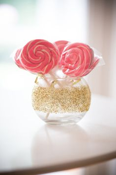 Glass round vase covered in gold glitter and filled with pink and white swirl lollipops - cute idea for the #wedding #candy bar or centerpieces.