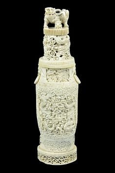 A CARVED IVORY COVERED VASE  Having a Fu dog finial surmounting the pierced lid with scrolling clouds and dragon motif, and having ringed figural mask form handles to each side, the body with carved elongated quatrefoil reserves depicting opposing dragons, between the scrolling surrounds, raised on a pierce carved integral base, and further raised on the pierce carved, fitted wood stand.