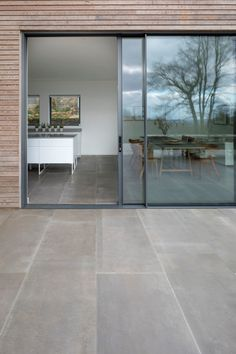 A large extension and refurbishment of a Georgian house in South Dartmoor. The n… A large extension and refurbishment of a Georgian house in South Dartmoor. The natural stone walls of the house have been exposed and the interior restored. The timber clad, House Extension Design, House Design, External Sliding Doors, Timber Sliding Doors, Aluminium Sliding Doors, Outside Flooring, Outdoor Flooring, Outside Tiles, Kitchen Sliding Doors