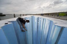 street art illusions- this is all chalk. he is standing on the pavement and bending over.