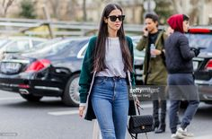 Gilda Ambrosio wearing a green cardigan blue denim jeans and a black Chanel bag outside Ellery during the Paris Fashion Week Womenswear Fall/Winter 2016/2017 on March 8, 2016 in Paris, France.