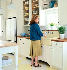 Beaded-board cabinet fronts on the bottom and glass-front cabinets above give the option for discreet storage as well as let the colorful dishware bring color into the space. Heart-pine countertops, a farmhouse sink, and pine floors painted a subtle yellow-and-white harlequin pattern give the kitchen an earnest cottage charm.