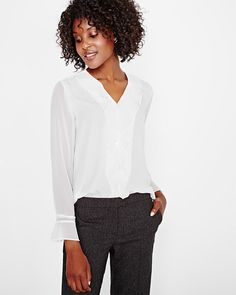 This light crepe blouse is perfect when paired with dress pants for the office or jeans after hours. <br /><br />- Soft and silky crepe fabric <br />- Long chiffon sleeve with buttoned cuffs <br />- V-neckline <br />- Chiffon ruffles along the placket